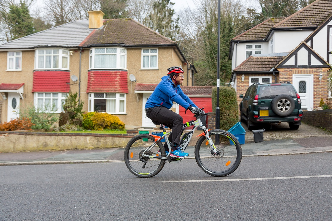 Robert, an e-bike rider in London, riding his e-bike up a steep hill on a residential street