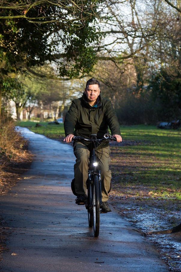 Philip, an e-bike rider in London, riding his e-bike on a shared-use path in a park
