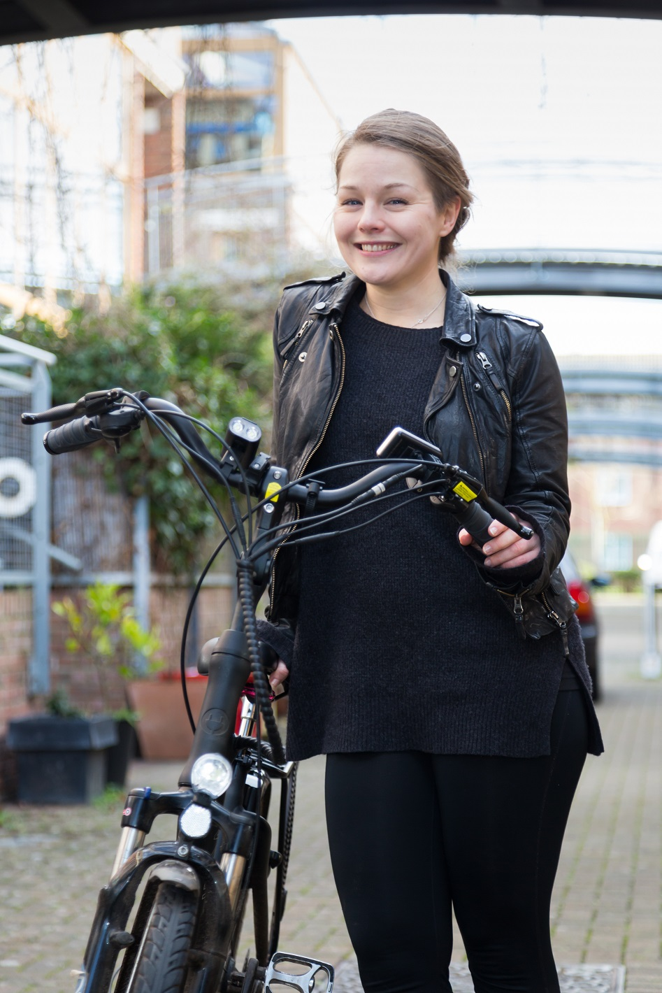 Marina, an e-bike rider in London, standing with her e-bike on a residential street with bridges connected the buildings overhead