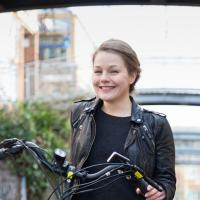 Marina, an e-bike rider in London, standing with her e-bike on a residential street