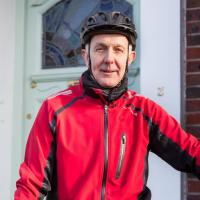 Paul, an e-bike rider in London, standing in front of his house wearing cycling gear